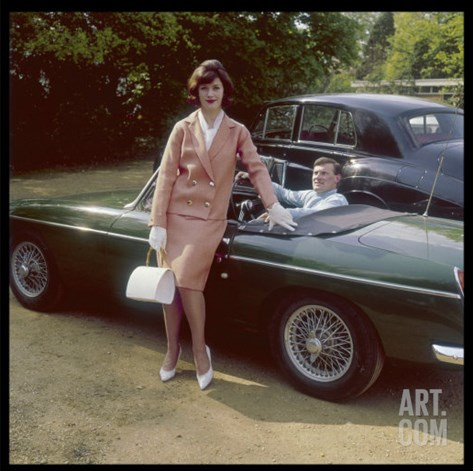Girl in a Smart Summer Suit Poses Next to Her Boyfriend's MGB Sports Car Stretched Canvas Print